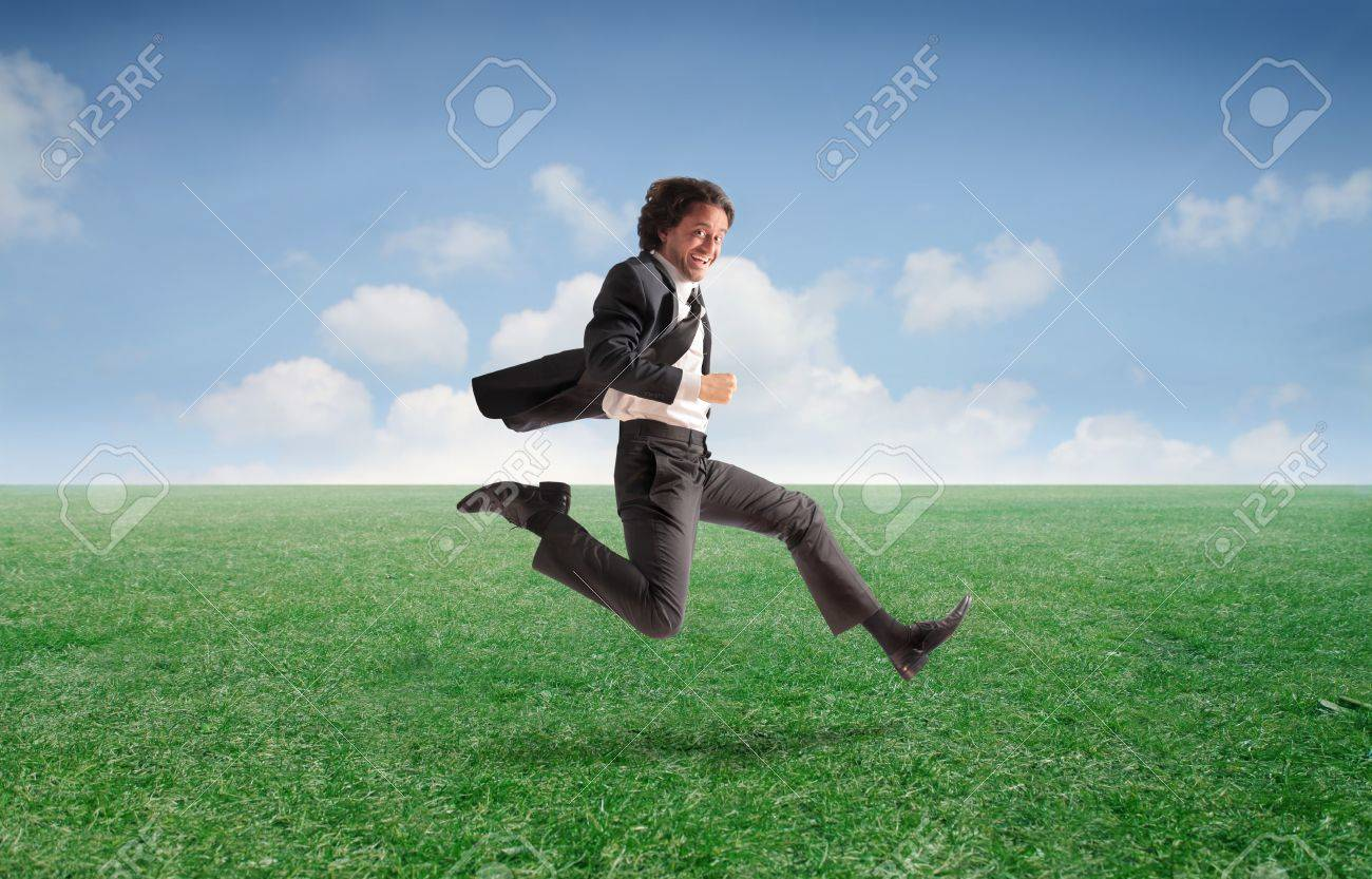 Smiling businessman running on a green meadow Stock Photo - 11571456