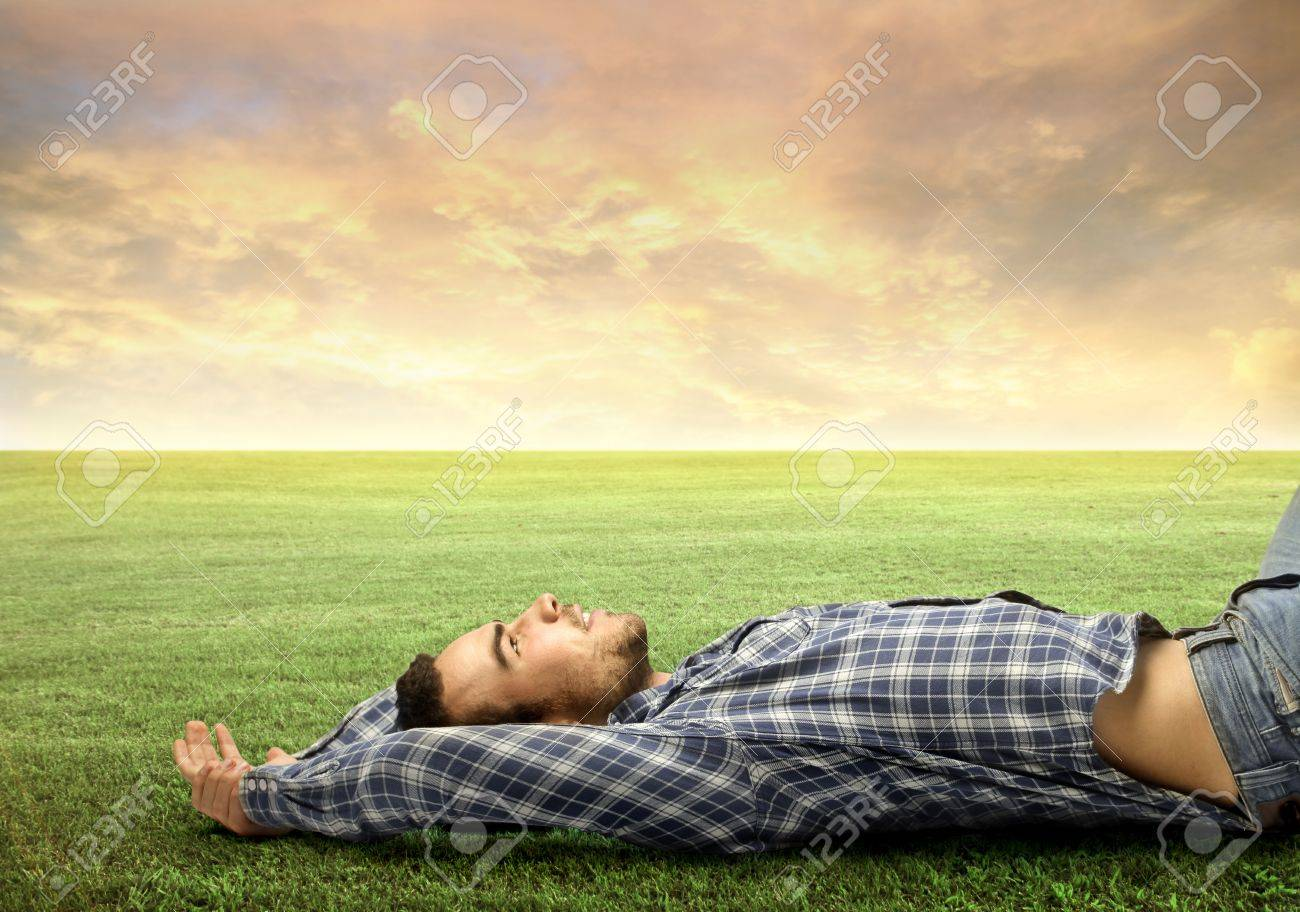 Young man relaxing on a green meadow Stock Photo - 11739409
