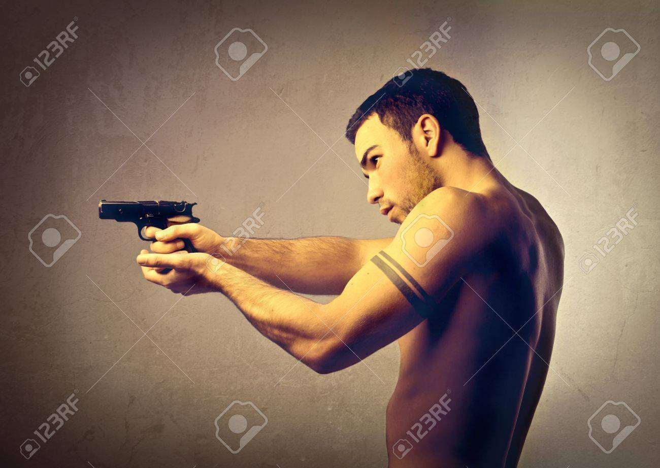 Handsome young man pointing a gun Stock Photo - 11739405