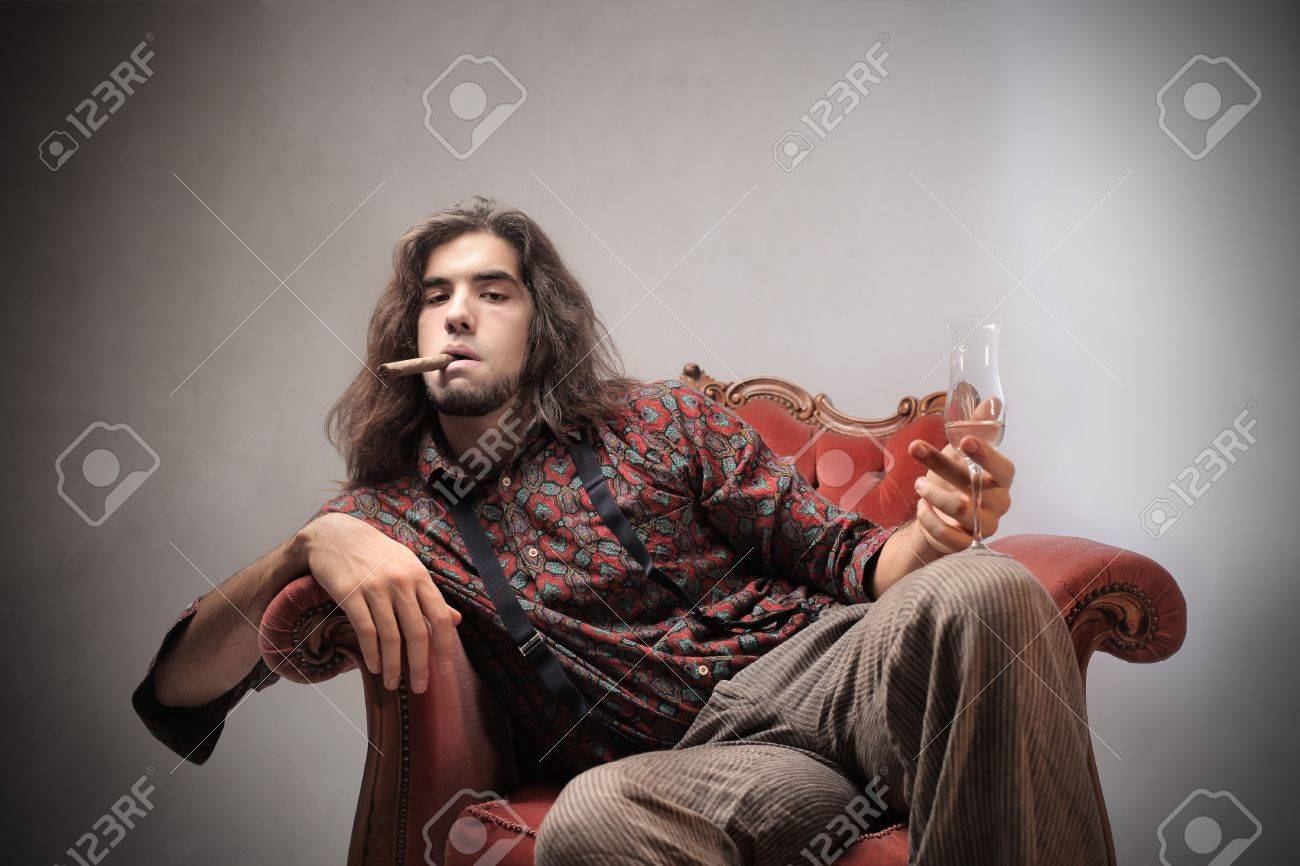 Bored young man sitting on an armchair and holding a glass of champagne and smoking a cigar Stock Photo - 11963283