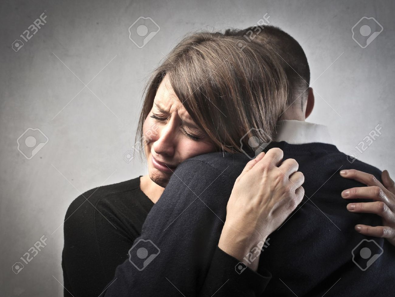 Sad woman crying on her husband s shoulder Stock Photo - 12648764