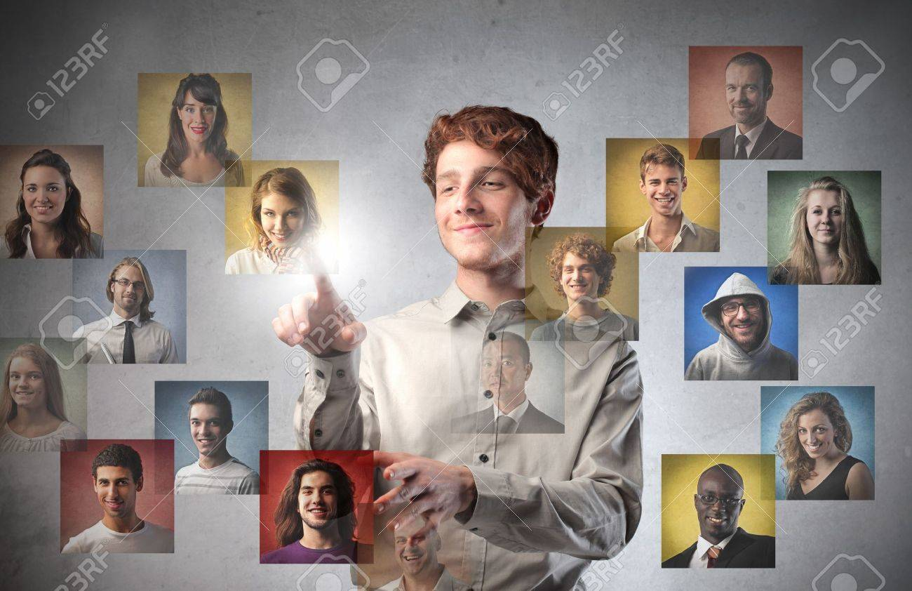 Smiling young man touching icons of different people on a touchscreen Stock Photo - 13281972
