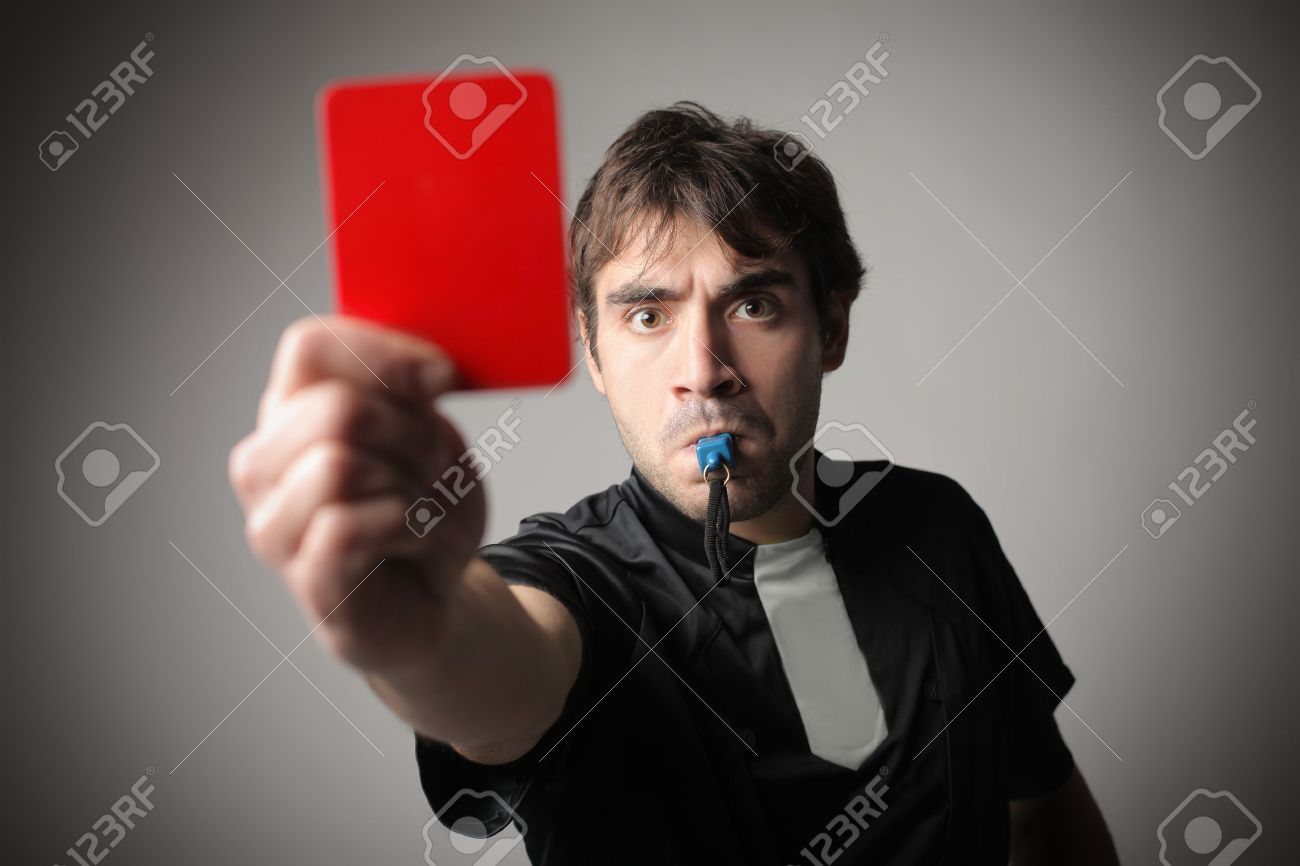 Angry referee whistling and raising a red card - 13639219