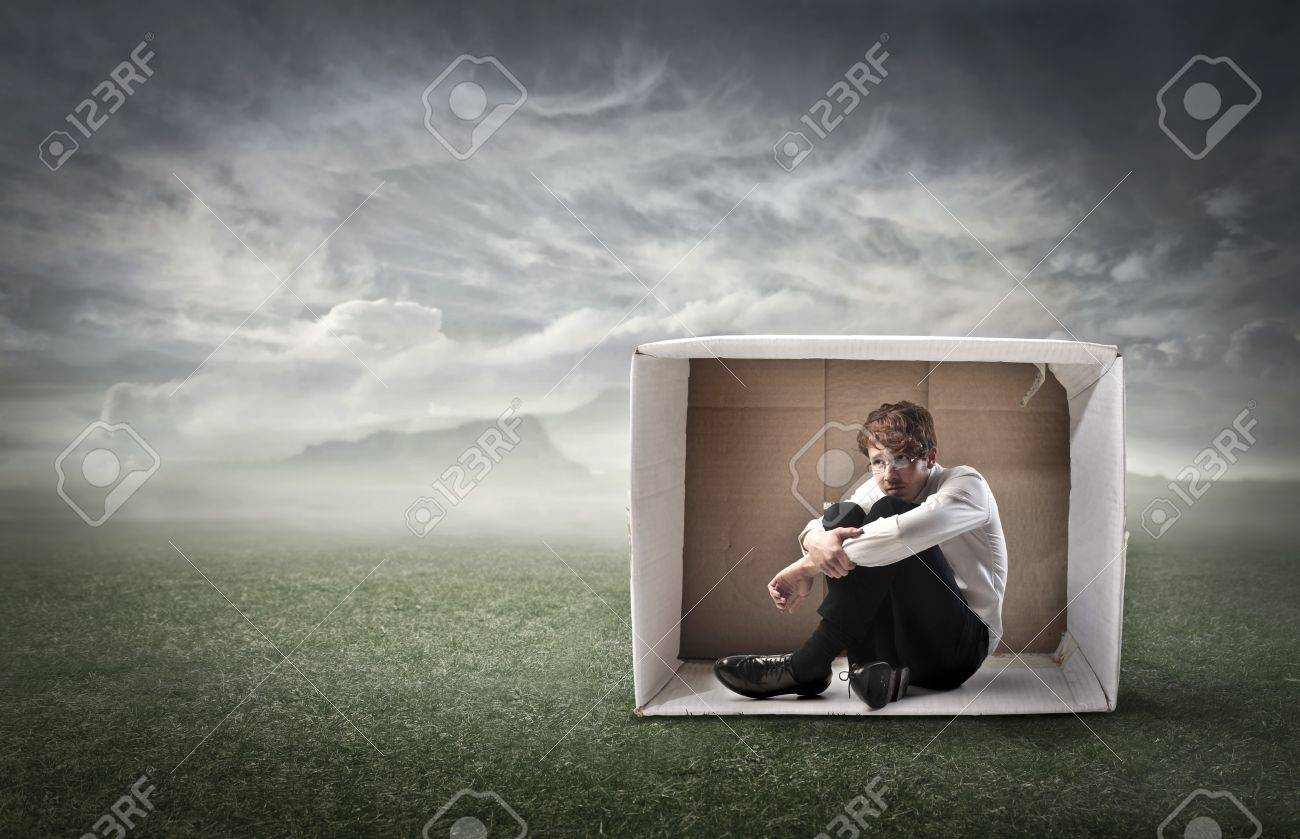 Sad young businessman sitting in a carton on a green meadow under stormy sky Stock Photo - 13656259