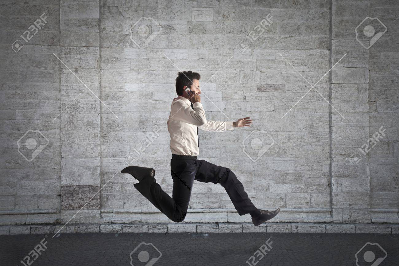 Businessman running while calling Stock Photo - 15112570