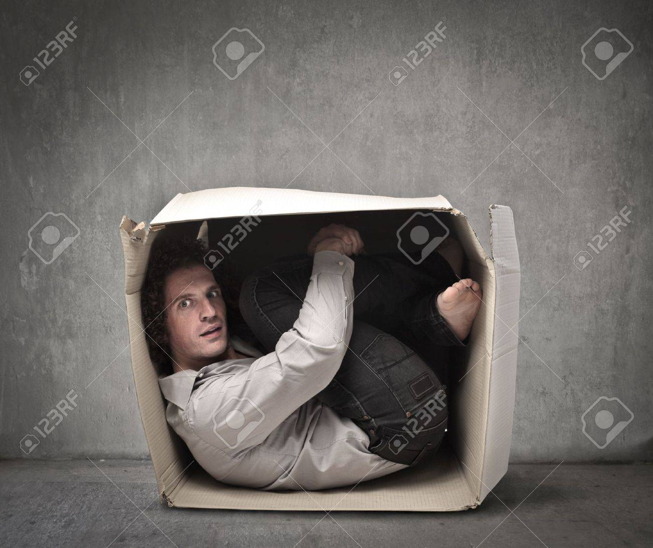 Man crouched in a box Stock Photo - 15662609