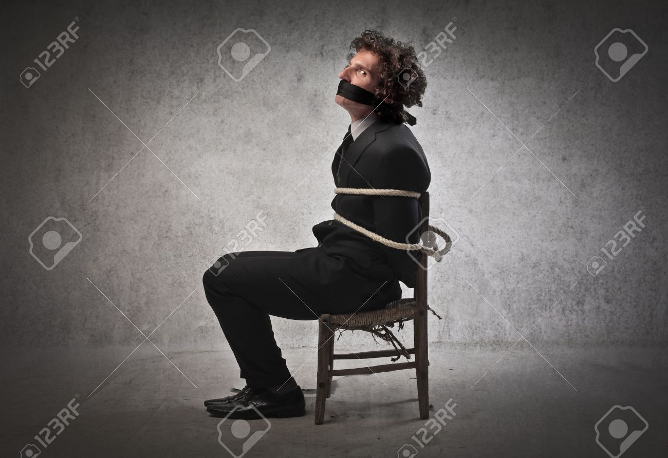 человек привязан к стулу фото
