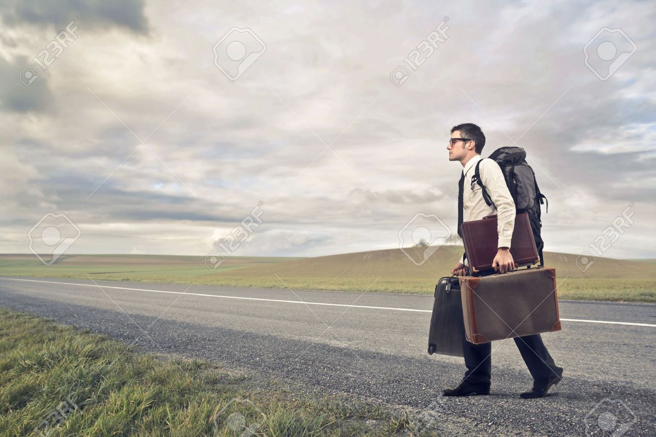 businessman with many suitcases walking on deserted road Stock Photo - 17482235