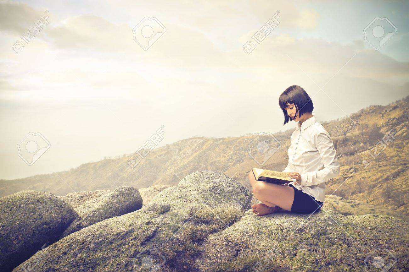 woman reading on a rock Stock Photo - 21802851