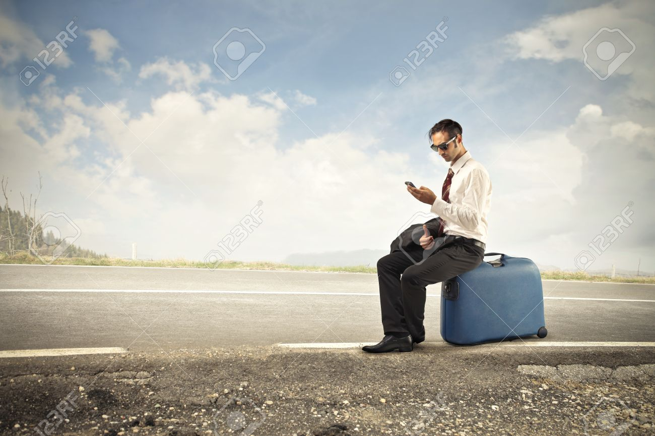 Businessman Waiting For Someone Sitting On His Suitcase Stock Photo
