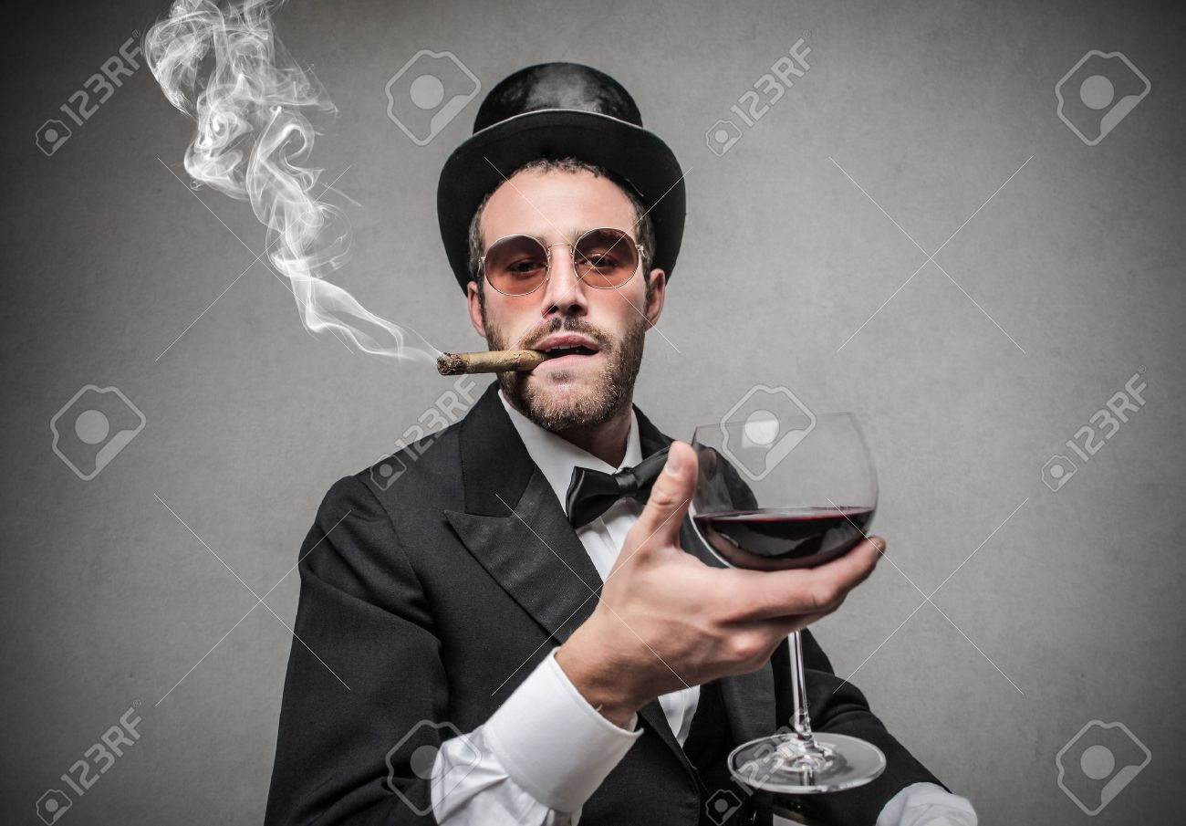 rich man holding a glass of wine and smoking a cigar Stock Photo - 22756646