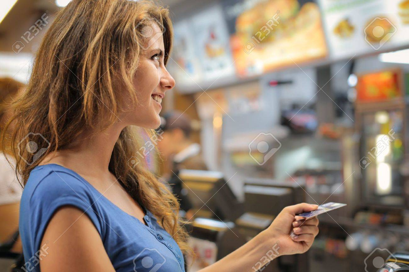Woman paying at a fast food restaurant Standard-Bild - 50740041