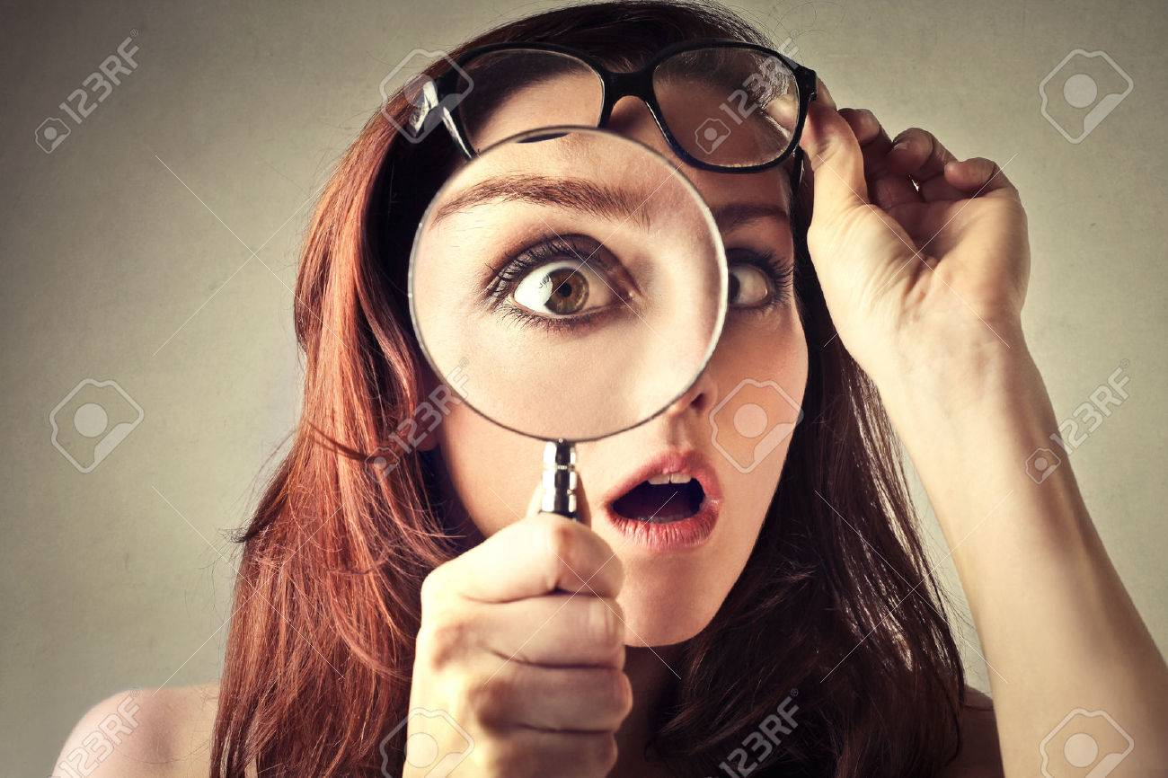 Young woman looking through magnifying glass Standard-Bild - 50740157