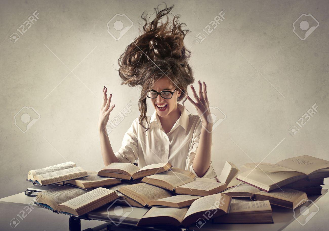 desperate woman trying to read books Standard-Bild - 50741042