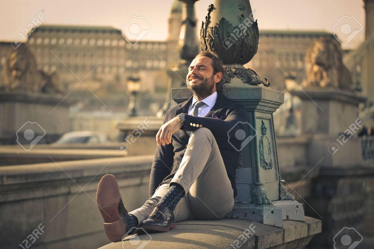 Happy businessman sitting outdoors Standard-Bild - 50742211