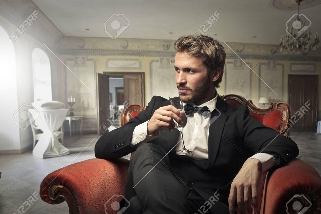 Handsome man sitting in an elegant room Standard-Bild - 58971239