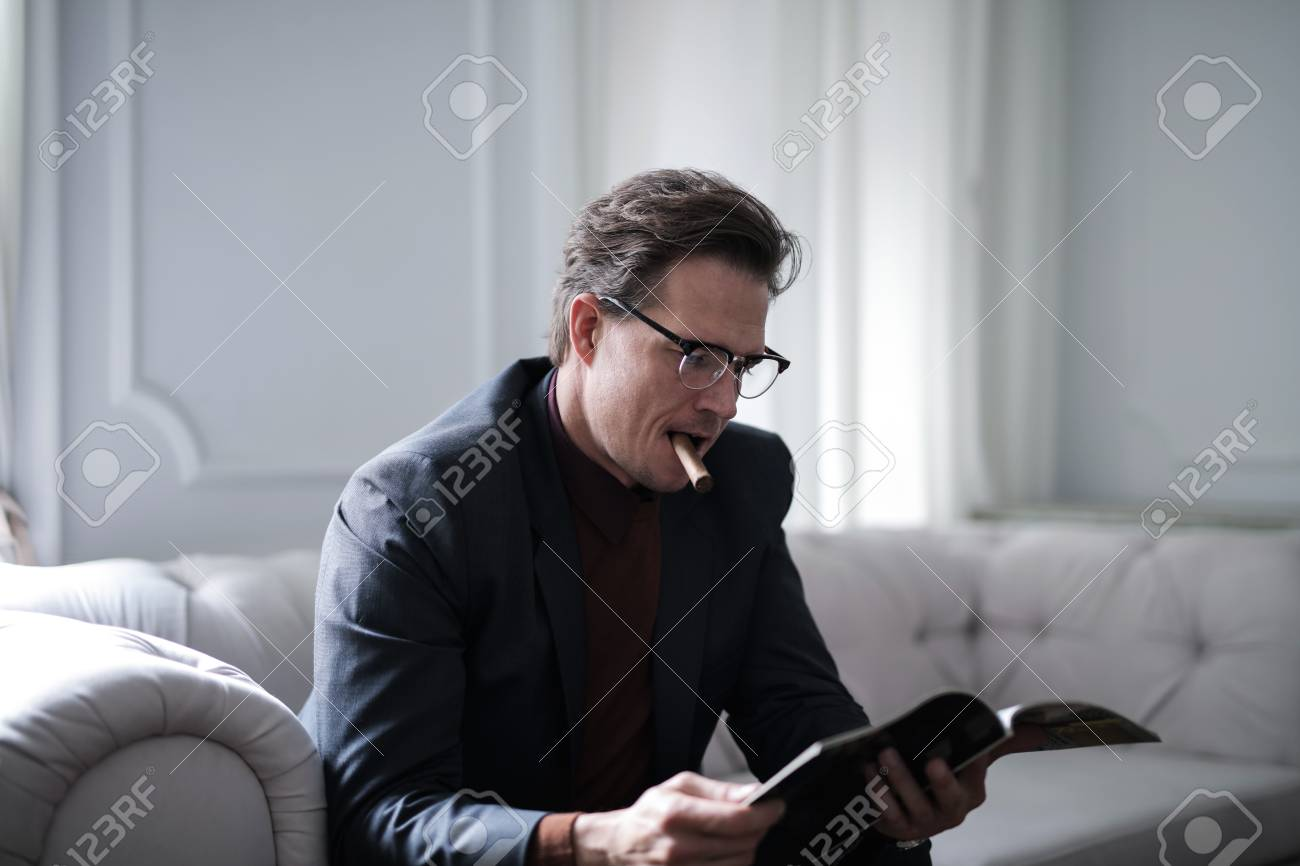 Man With A Cigar Reading A Magazine