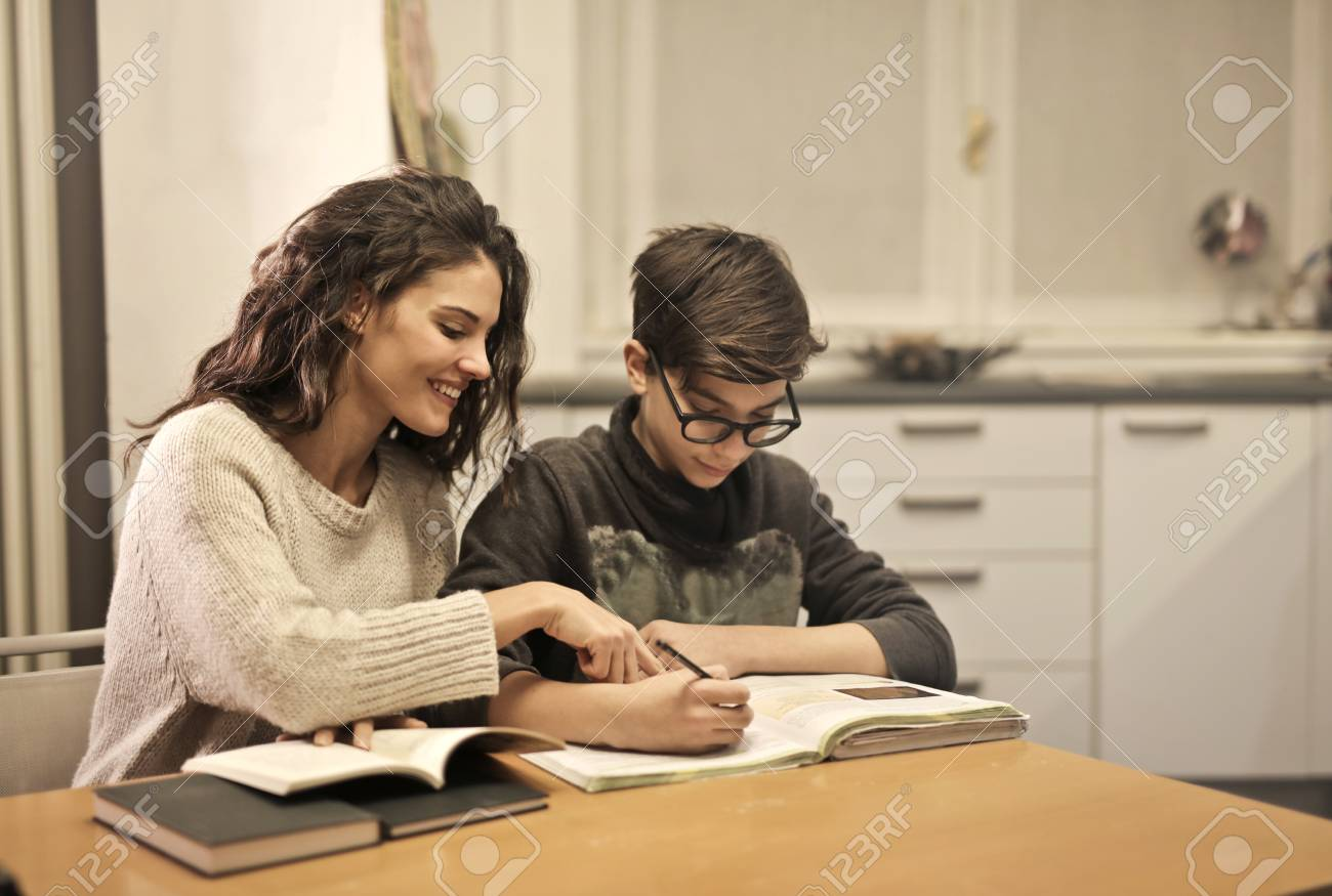 Girl helping a child with homework - 94801373