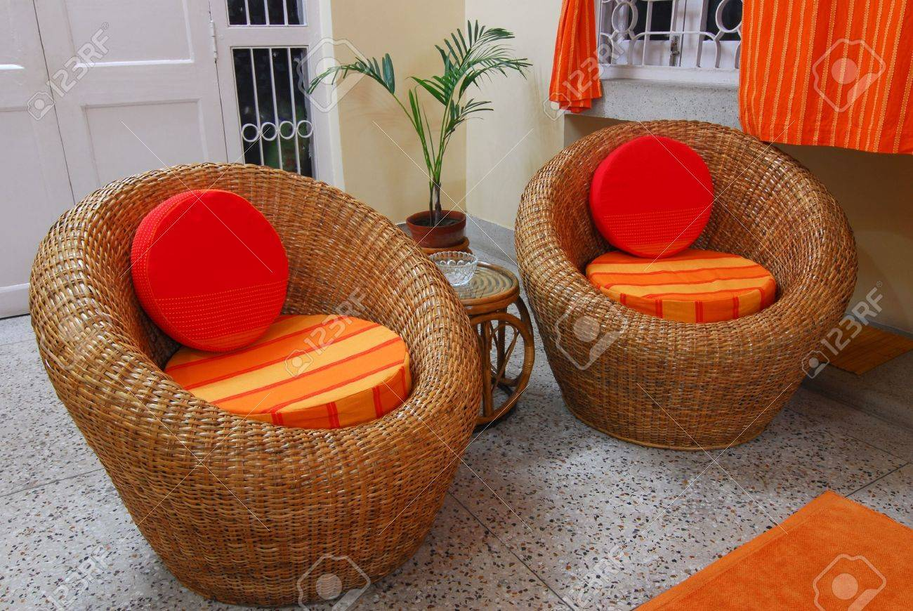 Cane furniture chair with orange cushions home interior stock photo 5668135