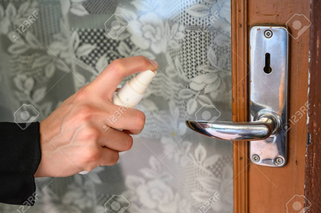 Shot of someone hand using alcohol hand sanitizer spraying on the door knob before open it. Hand sanitizer used to decrease infectious or kills germs, bacteria even more coronavirus. - 145259222