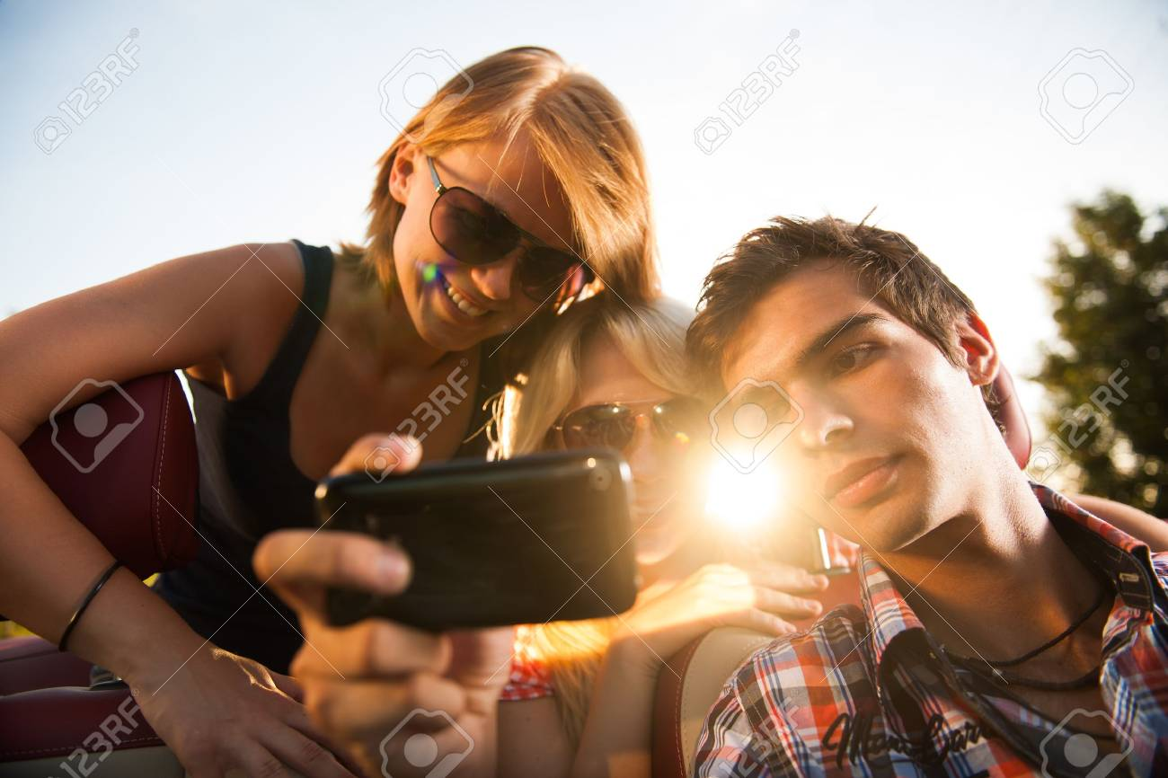 friends looking at a video on car Stock Photo - 17747251