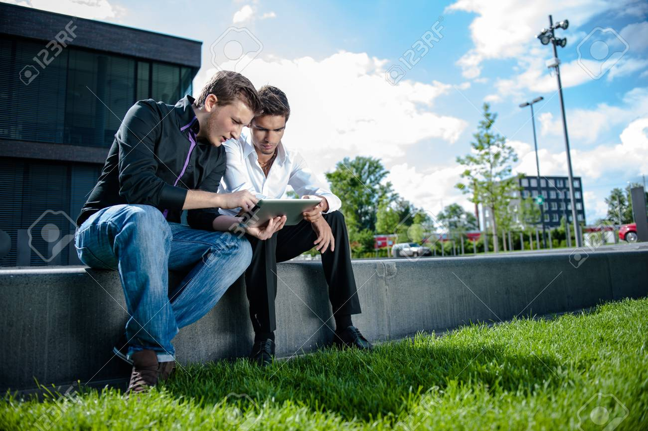 Two businessmen discuss a project on a tablet computer Stock Photo - 17718300
