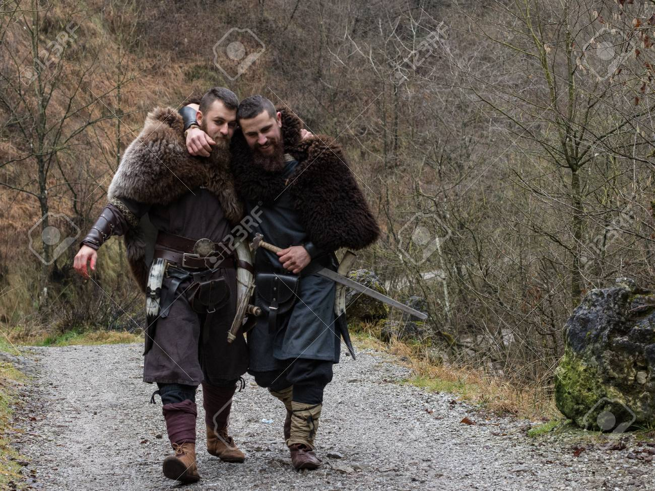 Two Viking Warriors Walk Hugged In The Forest