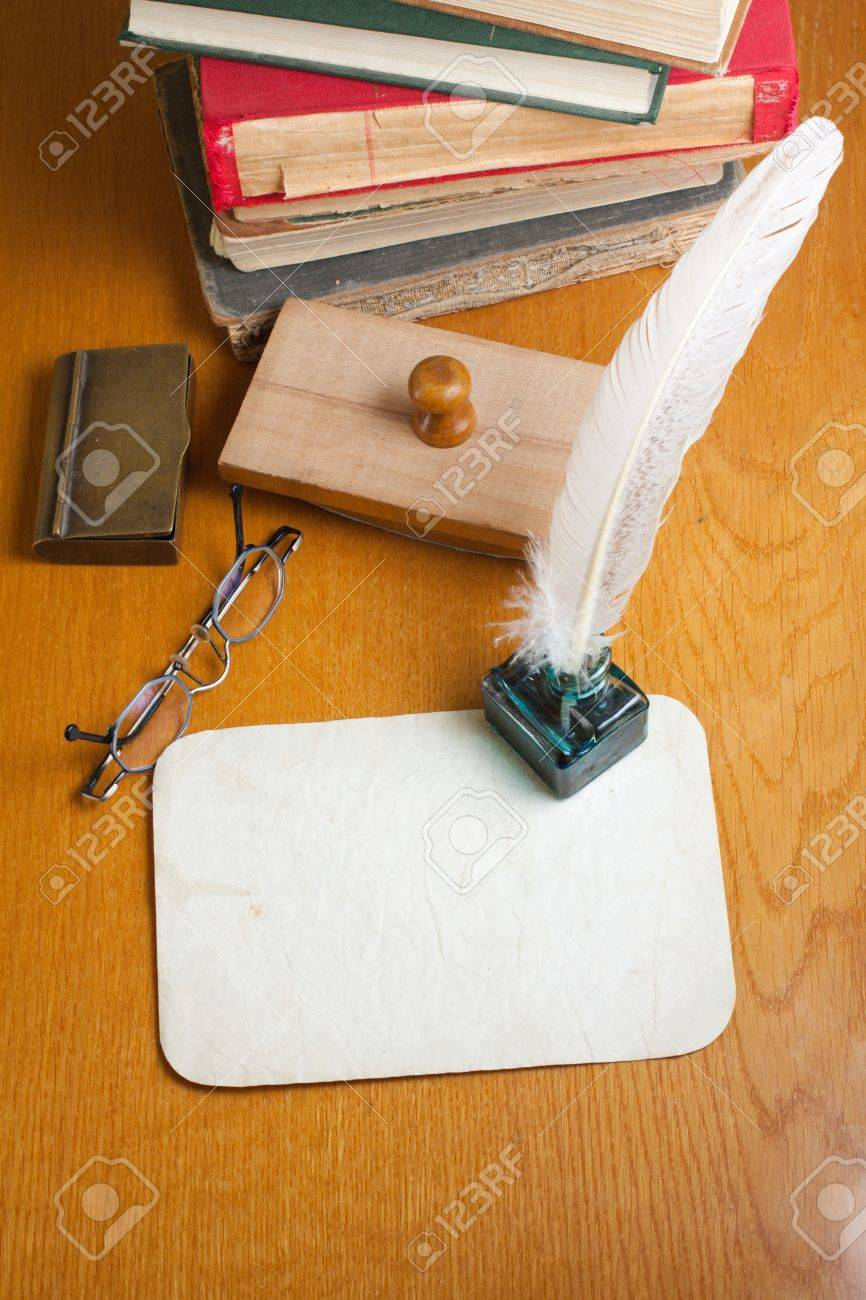 Grunge paper, quill and inkwell, old books, spectacles, blotter on wooden table Stock Photo - 13679074