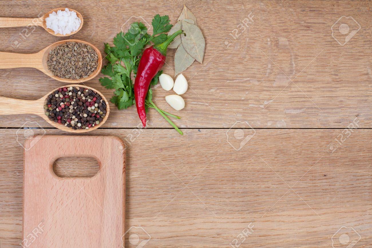 Kruiden in lepels, rode peper en een keuken plank op eiken houten ...