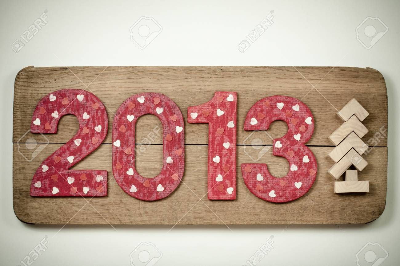 Retro New Year 2013 date and tree handmade on wooden board background Stock Photo - 16997757