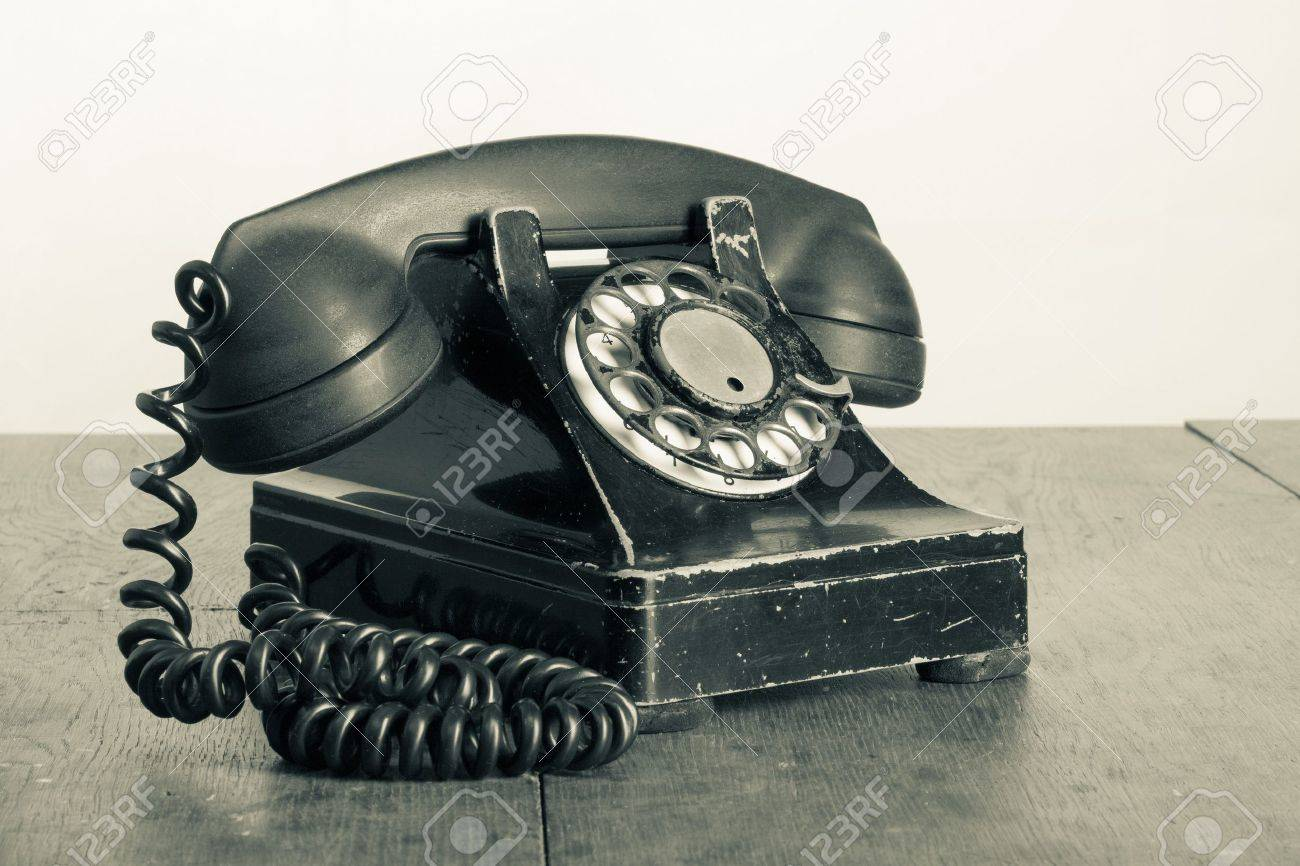 Vintage phone with rotary disc on old wooden table sepia photo Stock Photo - 17627805