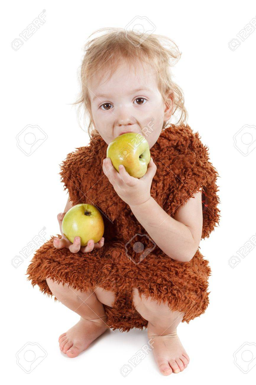 Little funny Neanderthal boy in a suit with a dirty face eating an apple. Humorous concept ancient caveman. Isolated on white. - 55644154