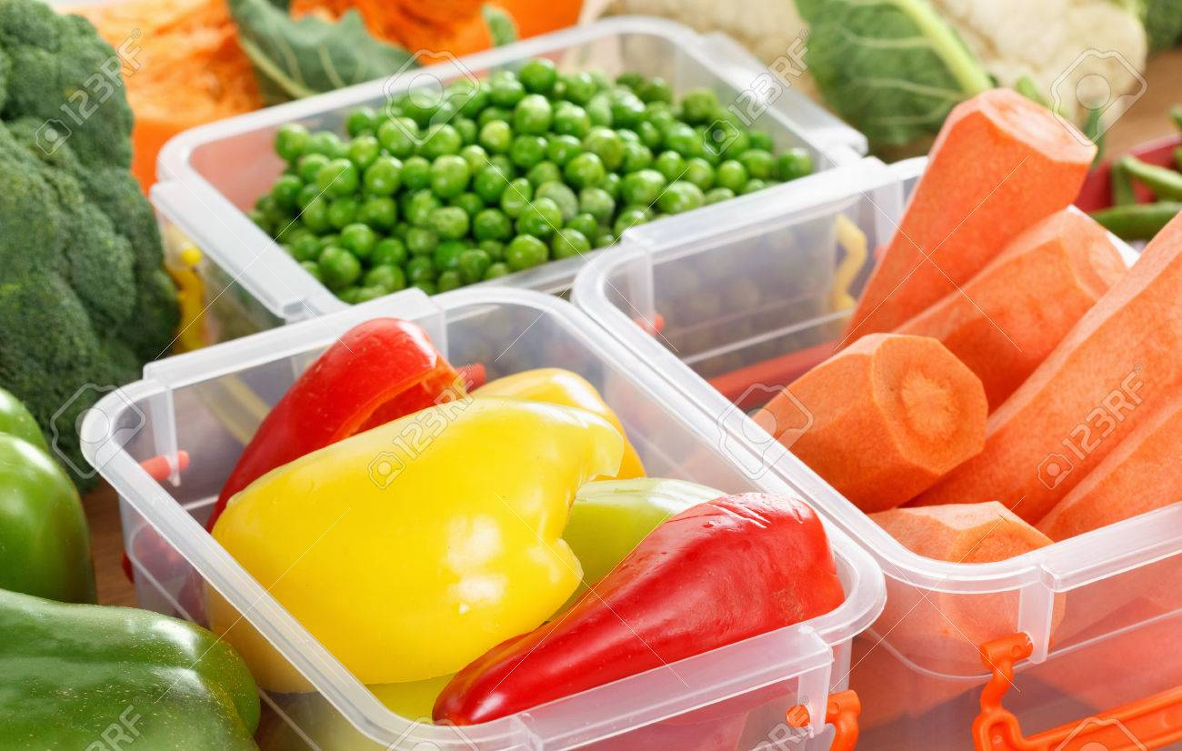 Trays with raw vegetables for freezing. Stocking up for winter storage in plastic containers - 65592041