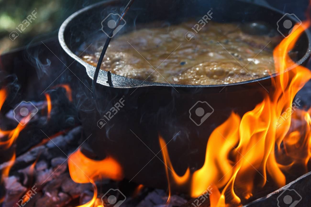 Tourist bowler with food on bonfire, cooking in the hike, outdoor activities. Preparation of pilaf or soup on fire. - 89837934