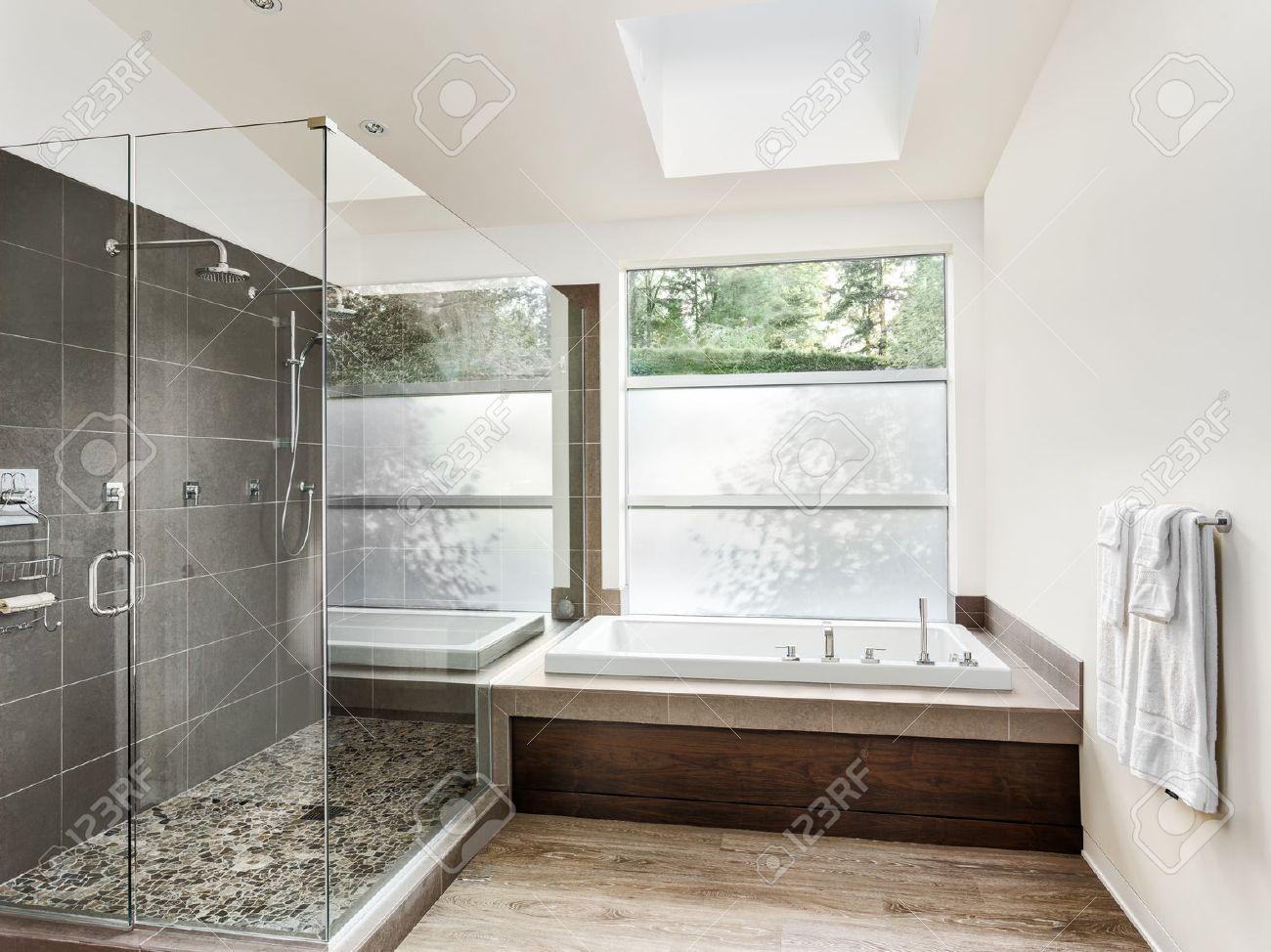 Bathroom interior in new luxury home: bathtub with walk in curbless..