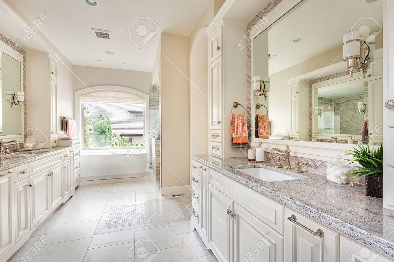 Grand intérieur de salle de bain dans la maison de luxe avec deux lavabos,  planchers de tuiles, les armoires de fantaisie, de grands miroirs, et ...