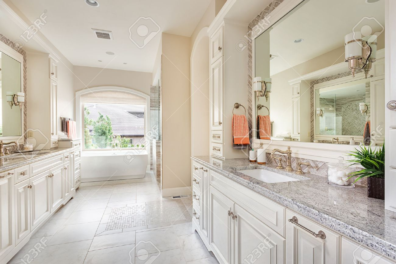 Large bathroom interior in luxury home with two sinks tile floors fancy cabinets