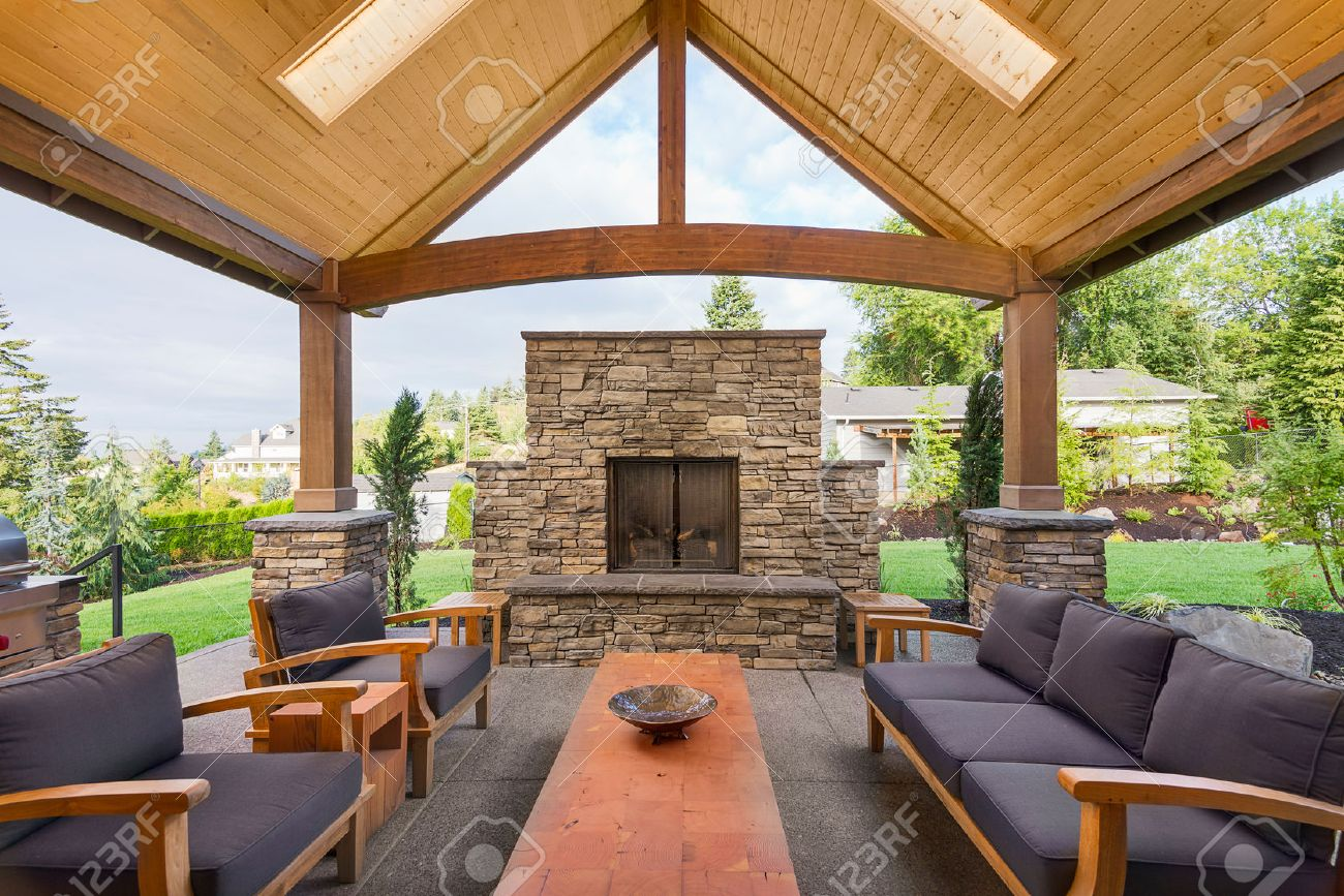 Covered Patio Outside Luxury Home With Large Stone Fireplace Table And  Couches Stock Photo
