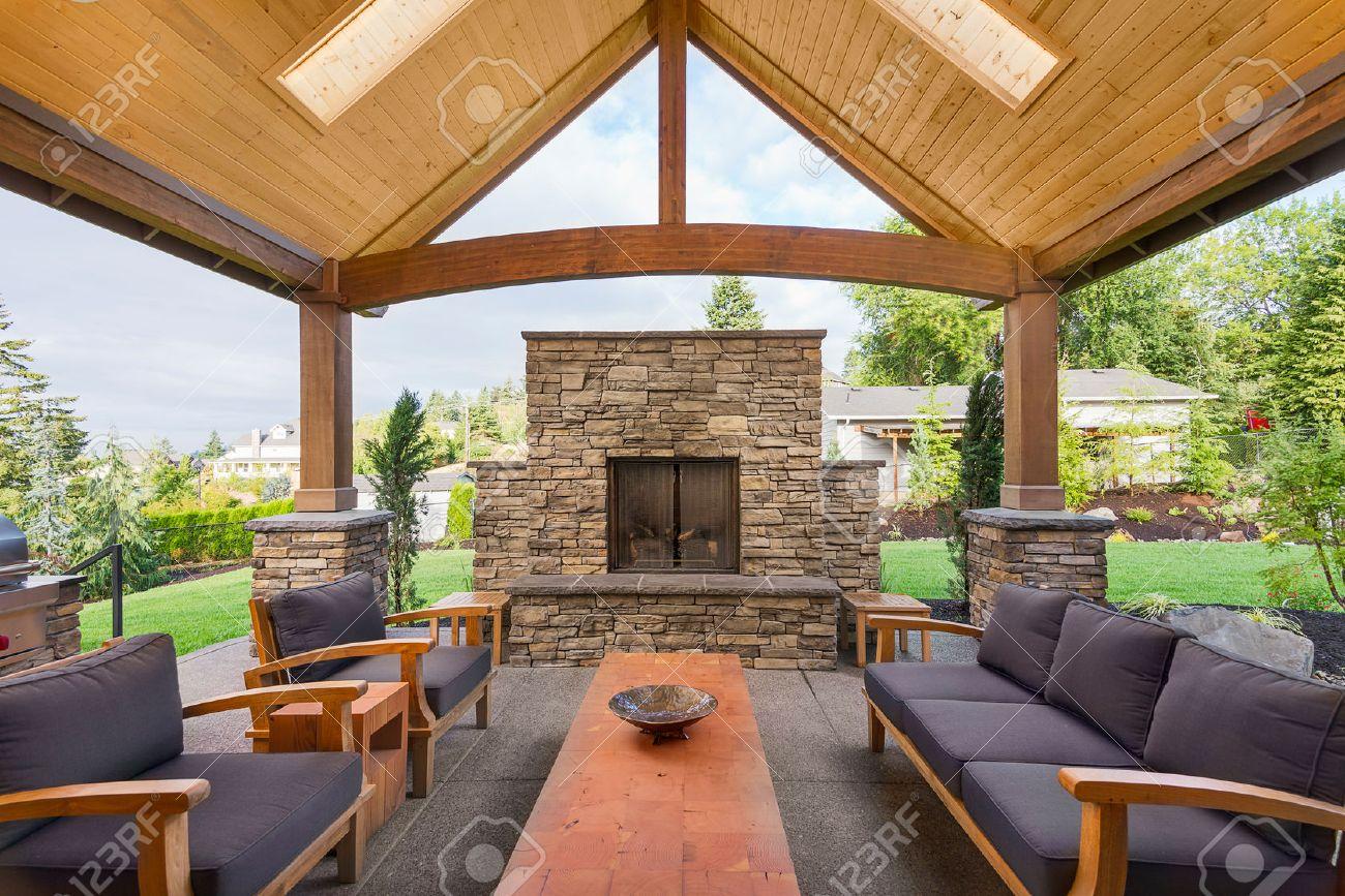 Terrasse couverte à l\'extérieur la maison de luxe avec grande cheminée en  pierre, table et canapés