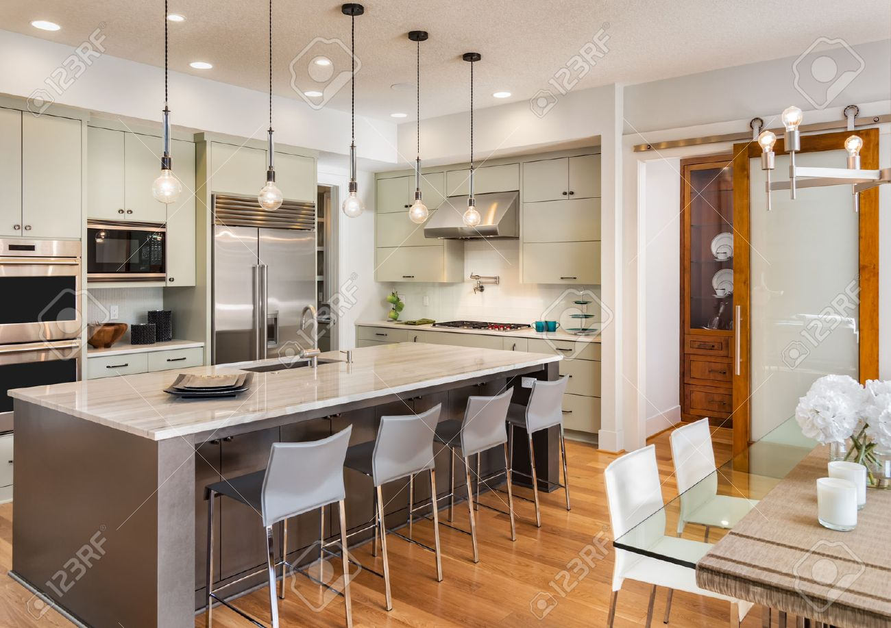 Kitchen Interior And Dining Room In New Luxury Home, With Island, Pendant  Lights,