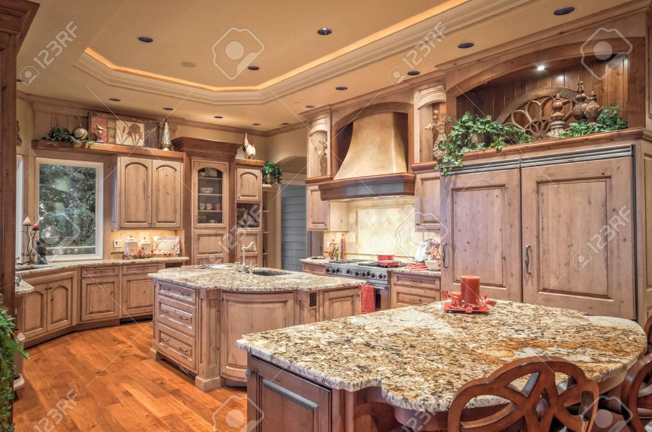 beautiful, large kitchen interior in new luxury home with island, refrigerator, range, hood, and hardwood floors - 50557116