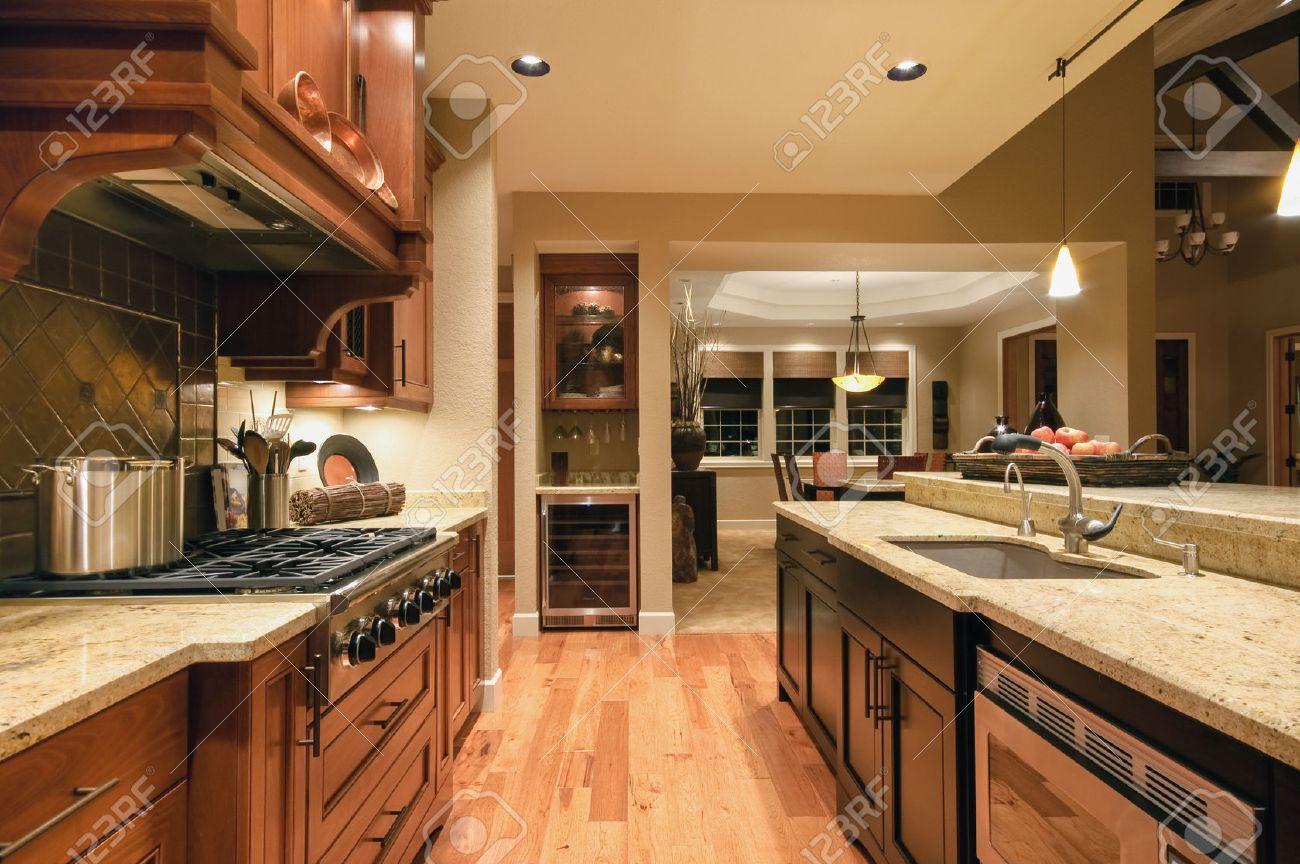 beautiful, large kitchen interior in new luxury home with island, refrigerator, range, hood, and hardwood floors - 50557139