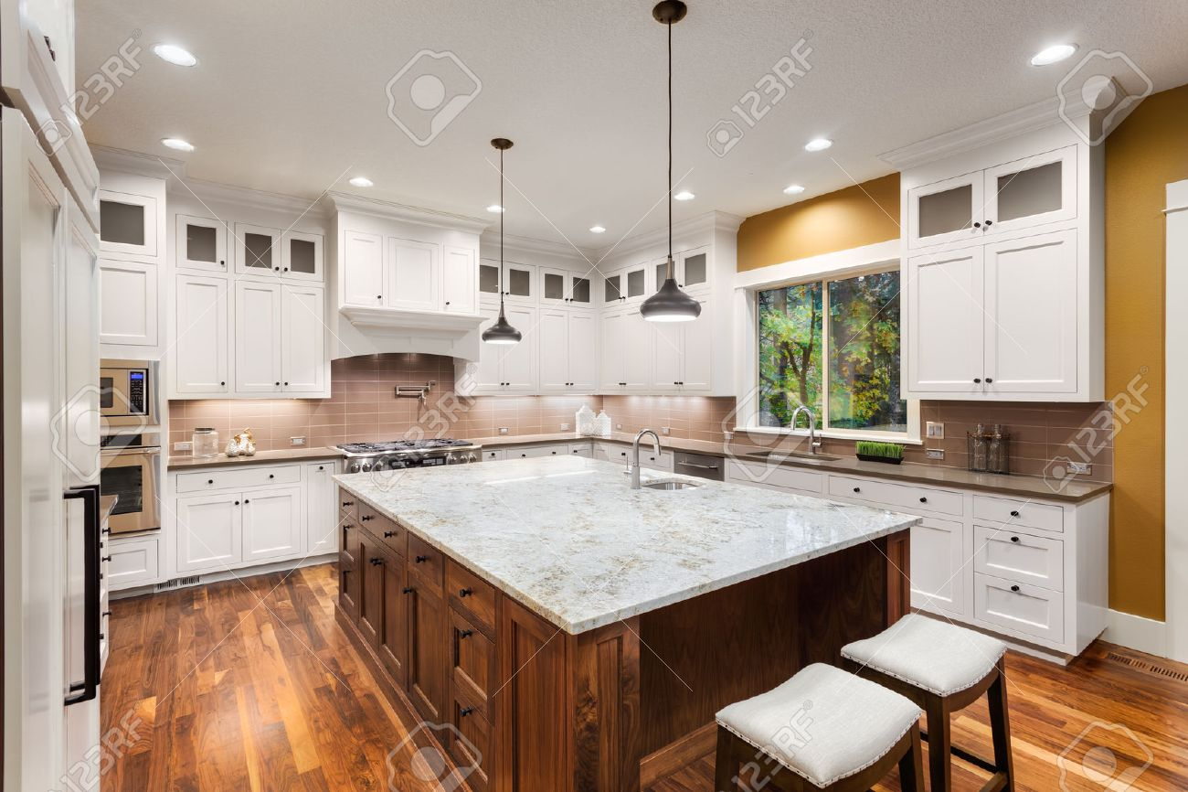 Large Kitchen Interior with Island, Sink, White Cabinets, Pendant Lights, and Hardwood Floors in New Luxury Home - 50834053
