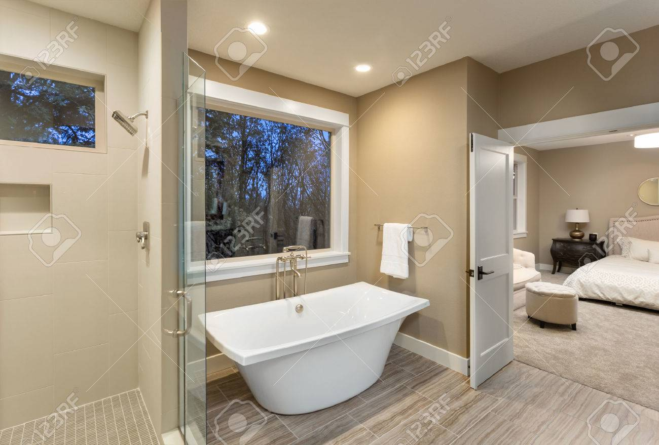 Beautiful Master Bathroom With Bathtub And Shower In New Luxury Home With  View Of Bedroom Stock