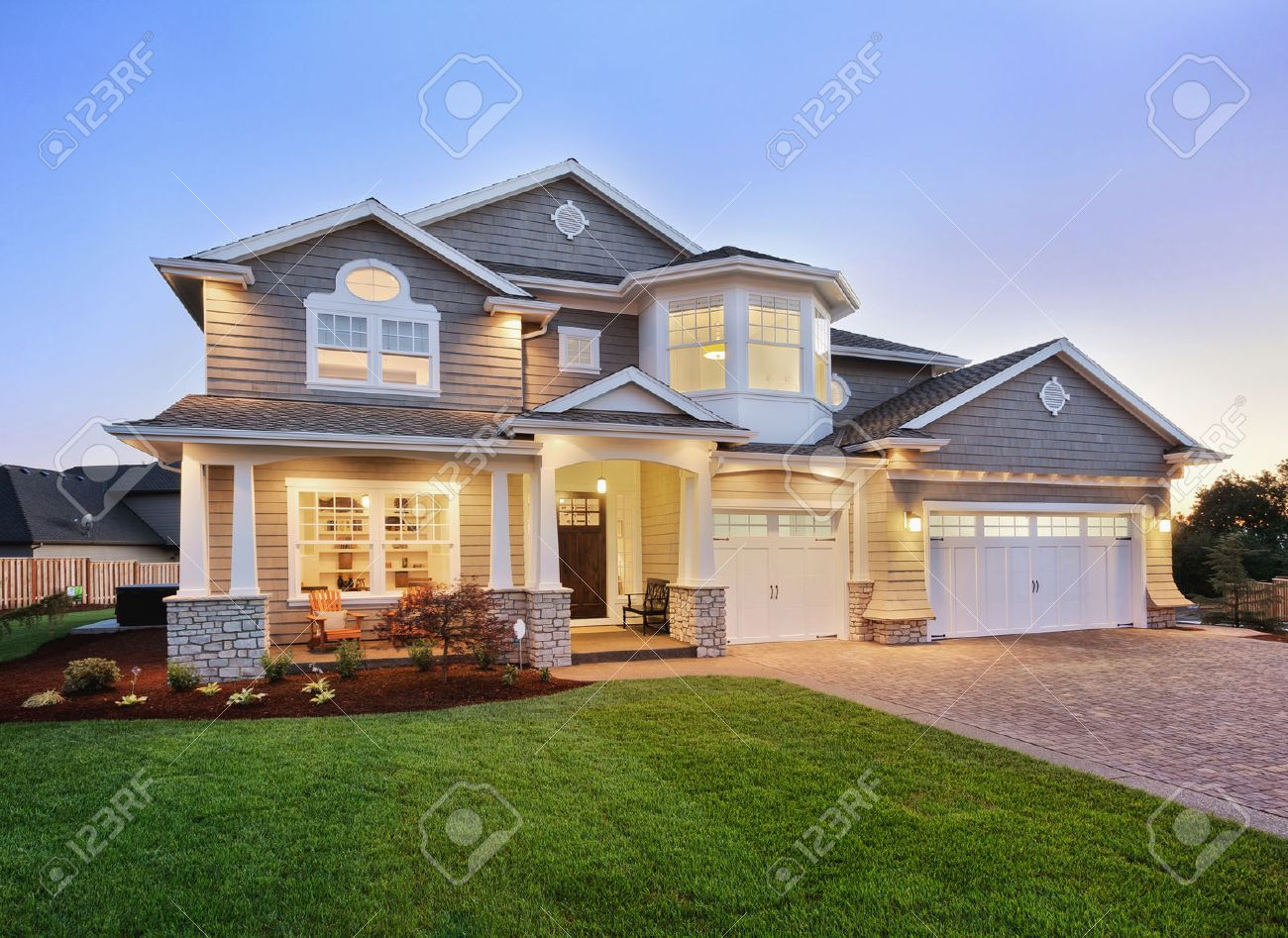 Home Exterior At Night/twilight With Beautiful Green Grass Three Car Garage,  And