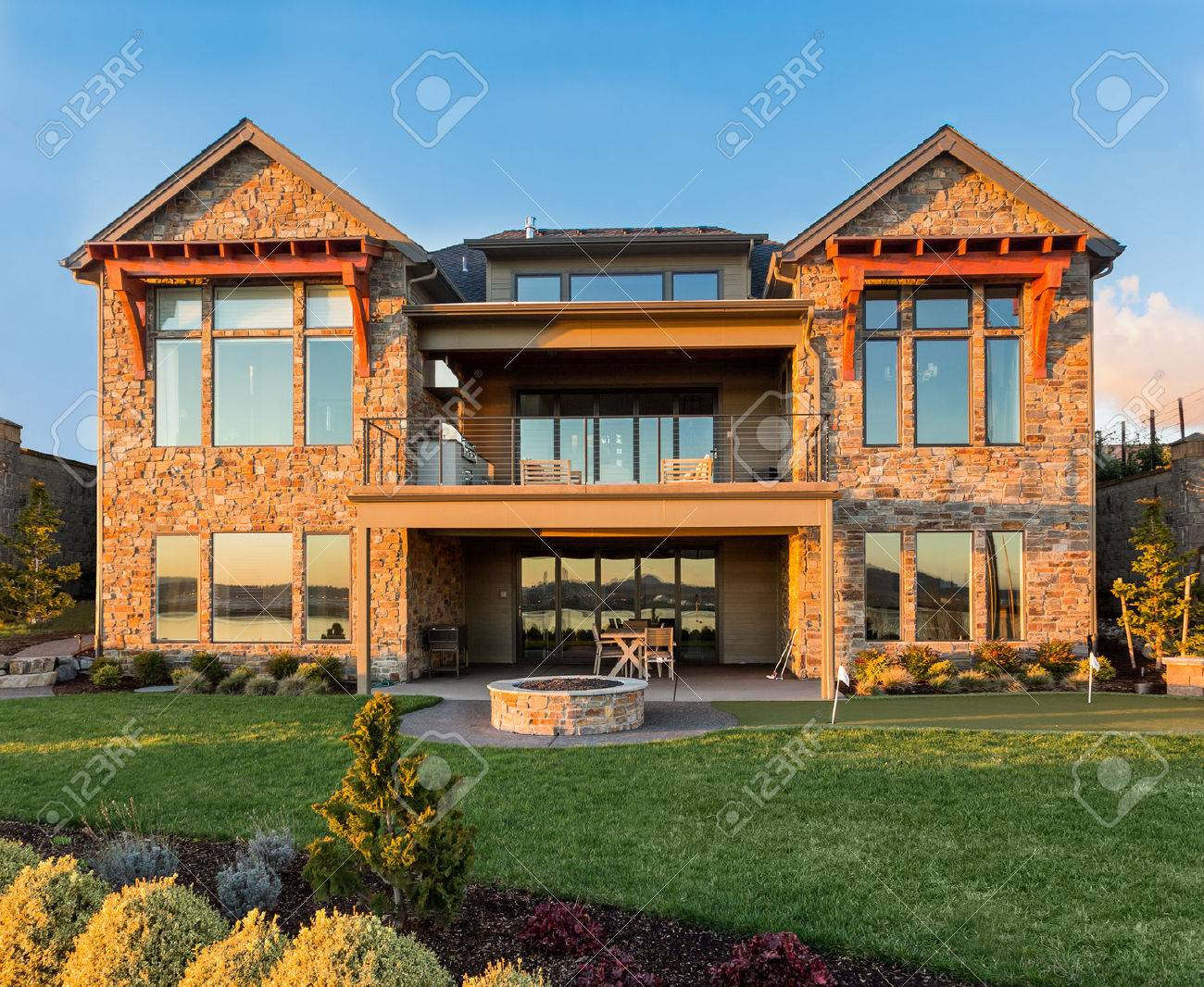 Beautiful Luxury Home Exterior With Balcony And Green Grass On