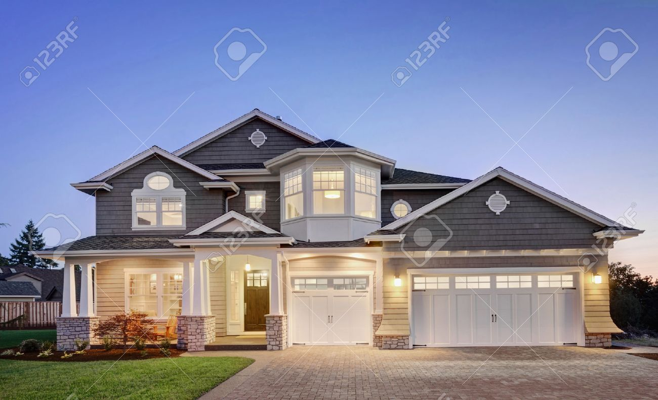beautiful luxury home exterior at night with three car garage driveway grass yard
