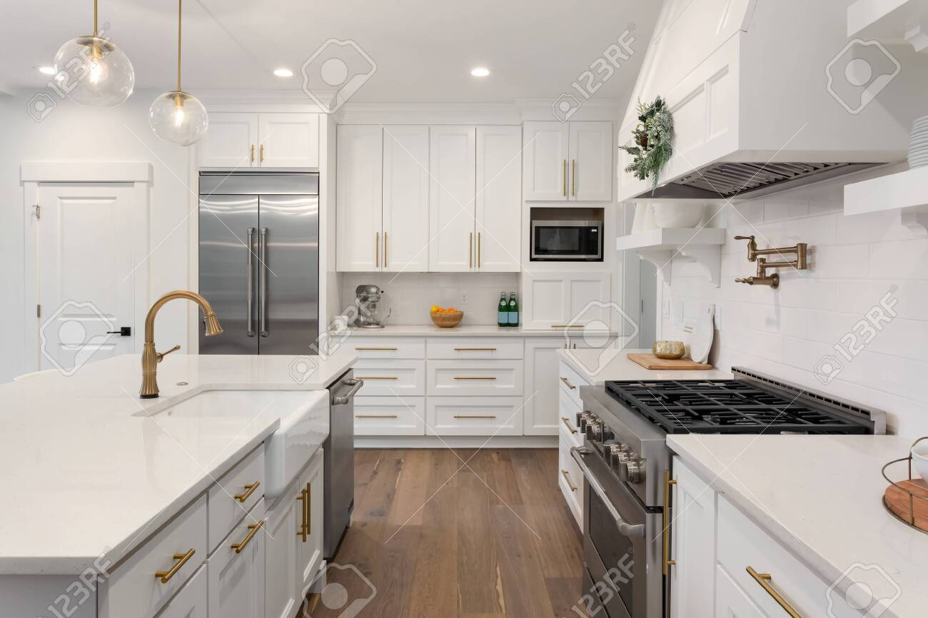 Beautiful kitchen with farmhouse sink and stainless steel appliances in new luxury home - 138971330