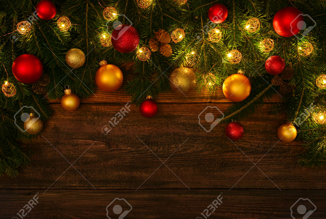 Close up fresh green spruce or pine Christmas tree branches with cones, lights, colorful balls and baubles decoration, over dark brown wooden planks background with copy space - 155953967