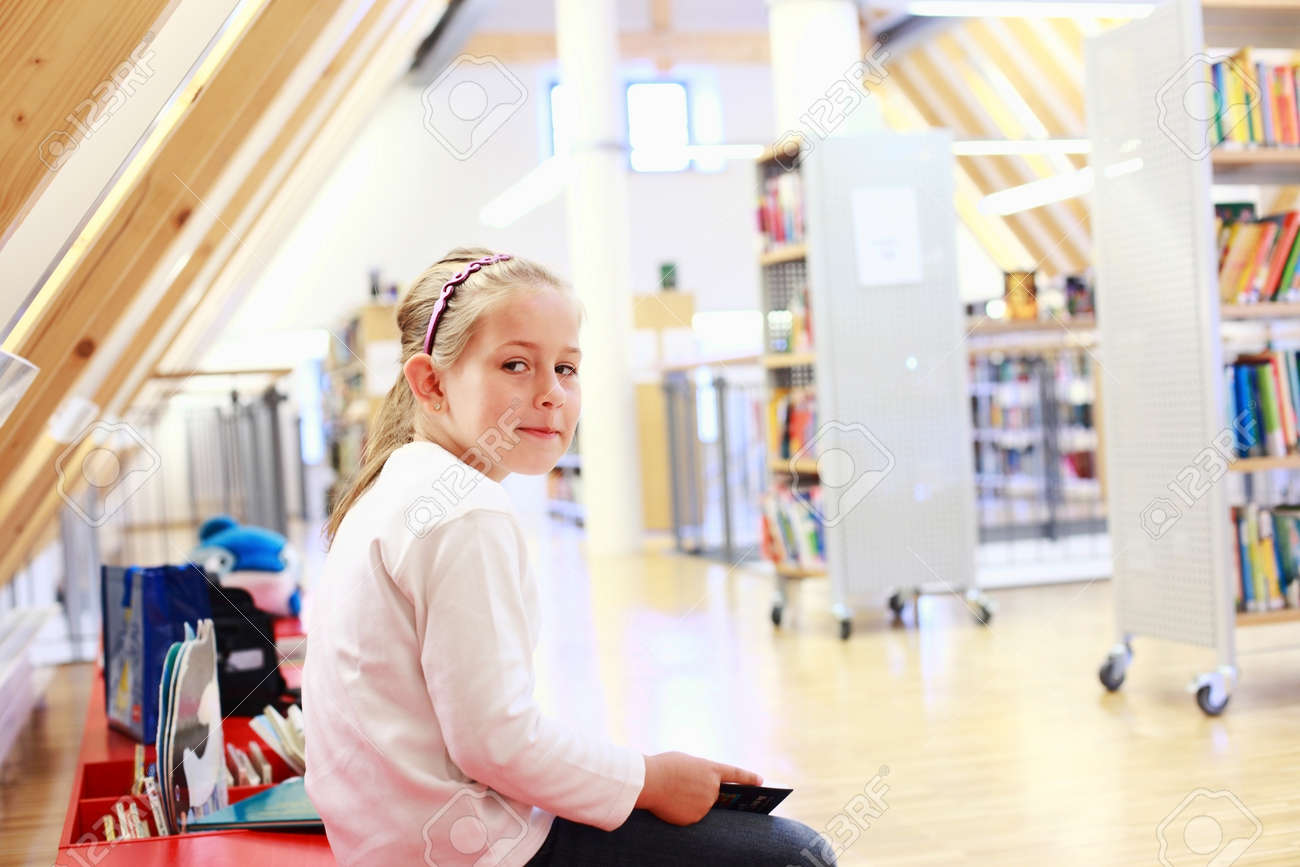 School girl reading a book in library Stock Photo - 10020643